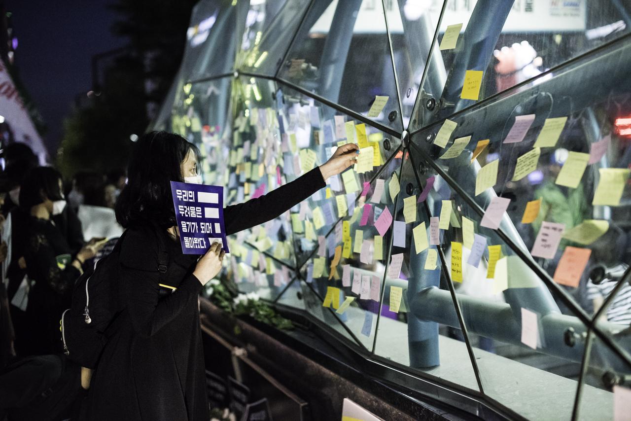 포스트잇을 붙이는 추모행진 참가자 한 참가자가 강남역 10번출구에 추모 포스트잇을 붙이고 있다.