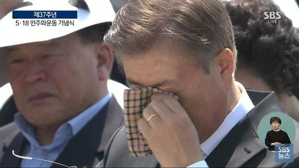 문재인 대통령이 18일 오전 광주 5.18 광주민주화운동 37주년 기념식장에서 1980년 항쟁 기간 동안 아버지를 잃은 김소정씨의 발언이 끝나자 체크무늬 손수건을 꺼내 눈을 훔치고 있다.