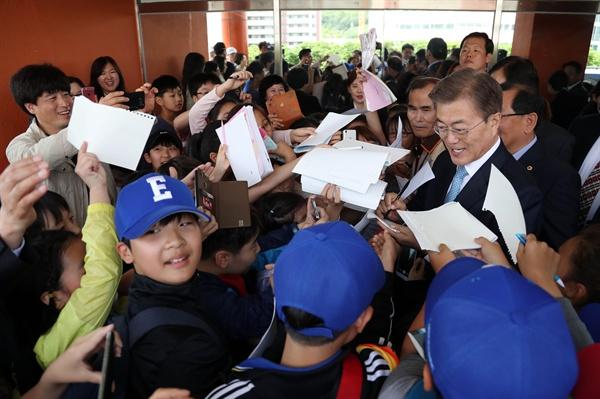 문재인 대통령이 15일 오후 서울 양천구 은정초등학교에서 열린 '미세먼지 바로 알기 교실' 행사를 마친 뒤 학교를 떠날 때 학생들이 문 대통령에게 사인공세를 펴고 있다.