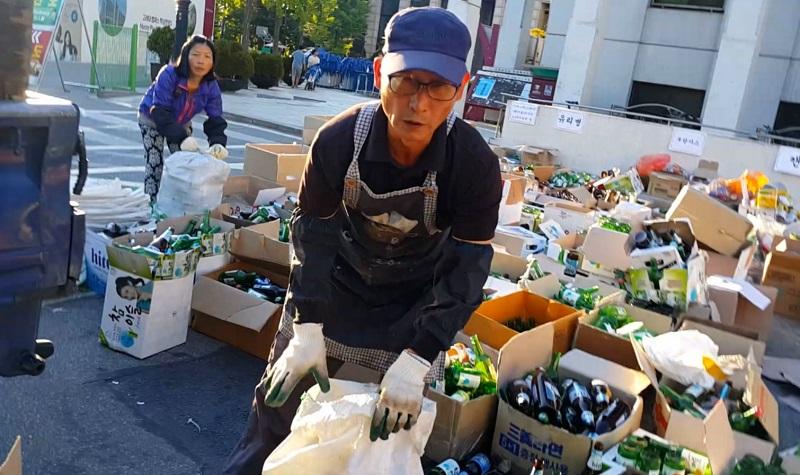 축제 하룻밤에 나온 술병 1만여 개를 수거하는 청소노동자들의 모습.