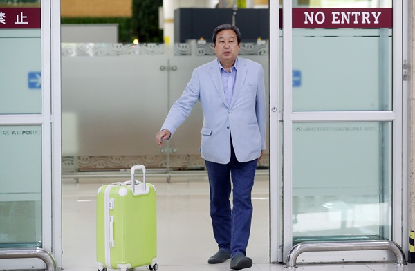 지난달 23일 오후 일본에서 귀국한 바른정당 김무성 의원이 서울 김포공항 입국장에 도착하며 마중 나온 관계자에게 캐리어를 밀어 전달하고 있다.