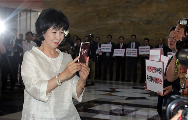 더불어민주당 손혜원 의원이 지난 5월 31일 오후 국회 본회의장에 입장하다 로텐더홀에서 이낙연 국무총리 후보자 인준반대 피켓시위를 하는 자유한국당 의원들을 휴대전화로 촬영하고 있다.
