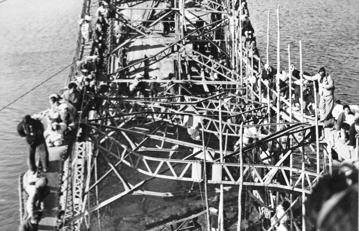 평양시민들이 부서진 대동강철교를 건너 남쪽으로 피란하고 있다(1950. 12.).