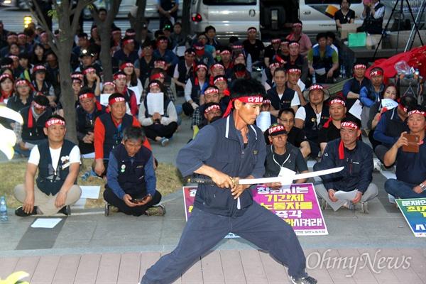 """민주노총일반노동조합 중부경남지부는 9일 저녁 창원시청 주변에서 """"창원시 복지포인트 삭감 규탄 및 기간제 노동자 정규직화 요구 결의대회""""를 열었고, 조영락 조합원이 칼을 들고 공연하고 있다."""