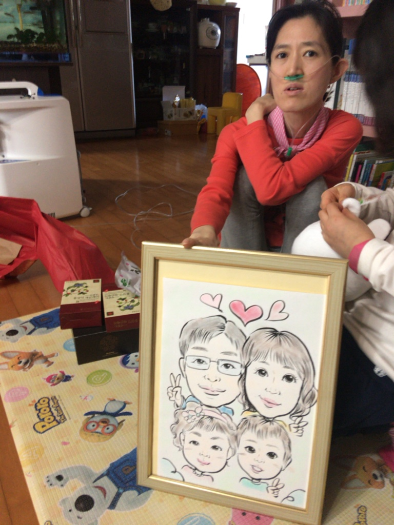 2016년 12월24일 크리스마스 이브, 환경보건시민센터 회원들이 환경피해 어린이와 가족들에게 작은 선물을 전하는 환경산타 프로그램으로 김포에 사는 윤미애씨 집을 방문했을때 산소호흡기를 착용한 윤씨가 단란했던 가족 캐리커쳐 그림을 보여주고있다. 2007년에 하늘나라로 간 첫째아이는 그림에 없다.