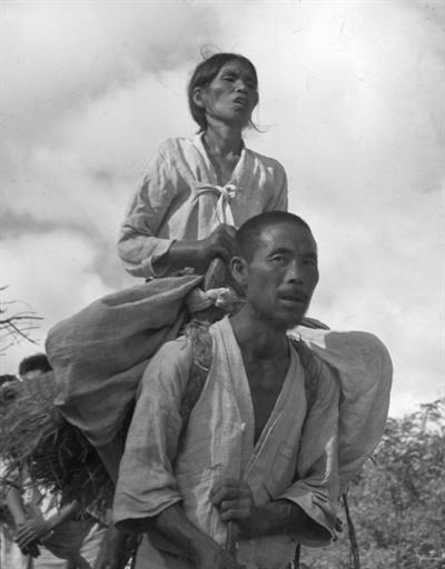 1950.9. 한 지아비가 시각장애인 아내를 지게에 진 채 피란길을 떠나고 있다.