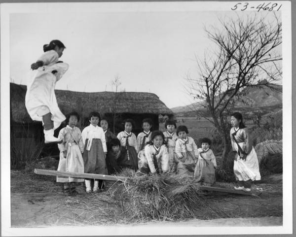 1953.2.19. 전란 중이지만 설빔을 차려 입은 천진난만한 소녀들이 민속놀이의 하나인 널뛰기를 하고 있다.