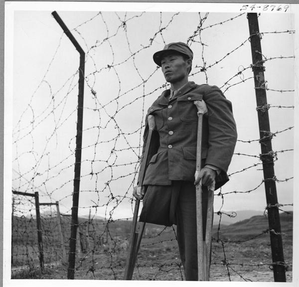 1950.10. 옹진전투에서 한쪽 다리를 잃은 한 국군 특무상사가 목발을 짚은 채 침통한 표정으로 철조망 앞에 서 있다.