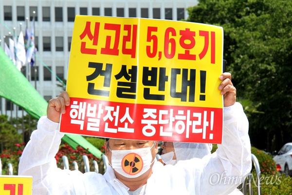한 시민이 '신고리원전 5,6호기 건설 백지화'를 요구하는 내용의 손팻말을 들고 경남도청 정문 앞에 서 있다.