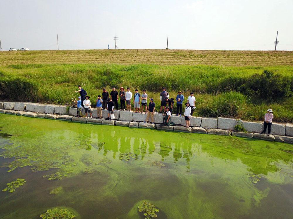 충남 논산시 금강에 창궐한 녹조밭에서 참석자들이 대화를 나누고 있다.