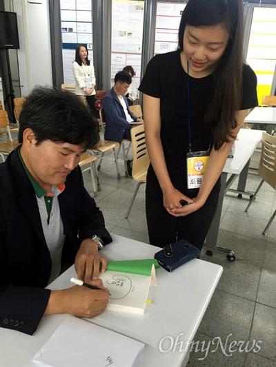 이민선 기자 (날아라 꿈의학교 저자)가 독자 요청을 받고 책에 서명을 하는 모습.