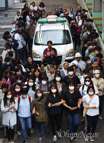2016년 9월 25일, 서울대병원 중환자실에서 장례식장으로 이동하고 있는 고 백남기 농민 운구 차량. 시민, 학생들이 경찰의 강제부검에 대비해 운구차량을 에워싼 채 장례식장으로 향하고 있다.