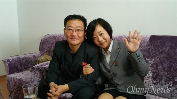 남한의 어머니에게 손을 흔들어 보이는 탈북동포 김련희씨의 딸 련금양과 김련희씨 남편.