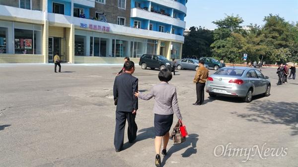 눈물을 글썽이며 버스정류장으로 걸어가는 아빠를 위로하는 탈북동포 김련희씨의 딸.