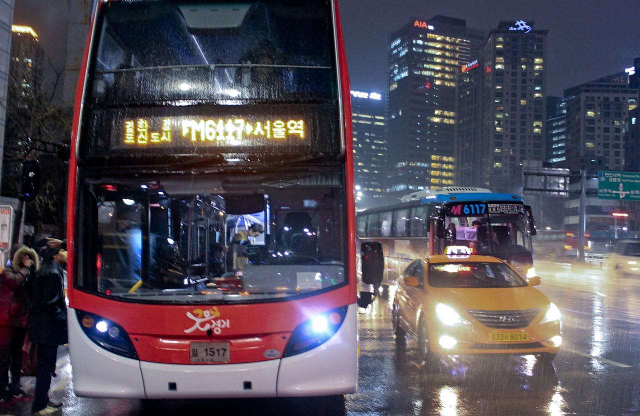 2014년 버스의 좌석 문제를 해결하기 위해 시범운행했던 M6117번 2층버스. 뒤로 M6117번 1층버스 차량이 지나고 있다.