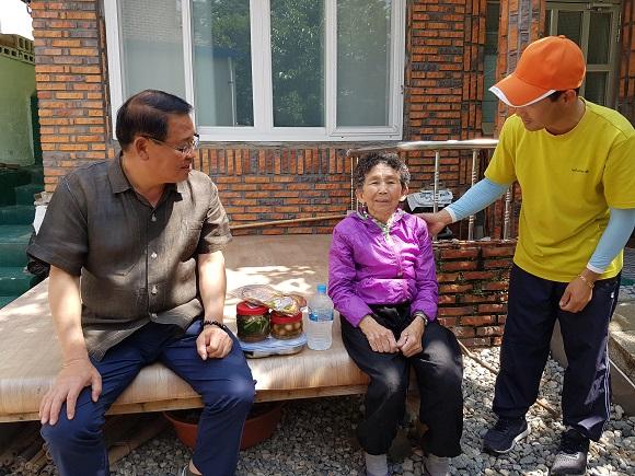 김성수 회장<왼쪽>이 할머니와 이야기를 나누고 있다.