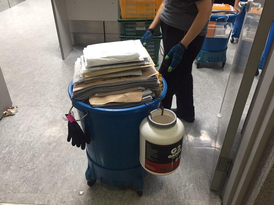 5일 오전 7시께 한 청소노동자가 신문과 우편물을 의원실로 옮기고 있다