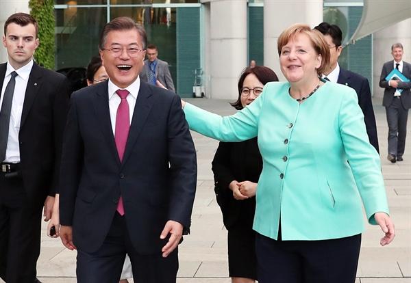 문재인 대통령이 5일 오후(현지시간) 독일 베를린 연방총리실 청사에서 앙겔라 메르켈 독일 총리와 함께 만찬 회담을 마치고 나오다 환영나온 한국 교민들을 보고 메르켈 총리와 함께 교민들을 향해가고 있다.