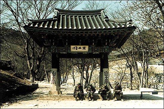 병사들이 건봉사 불이문 아래에서 겨울 햇살을 받으며 도란도란 이야기를 나누고 있다. 건봉사 일대가 군사 지역이라는 사실을 말해주는 듯한 풍경이다.