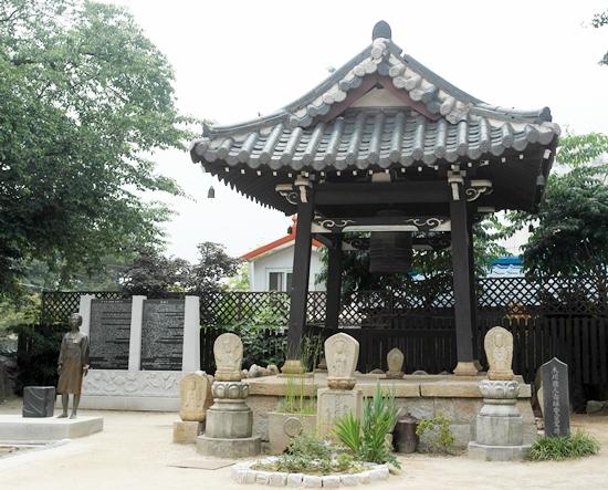 국내 유일의 일본 전통양식 종각, 왼쪽으로 참사문비와 평화의 소녀상이 보인다. 오른쪽에는 상록향 영가비가 세워져 있다.