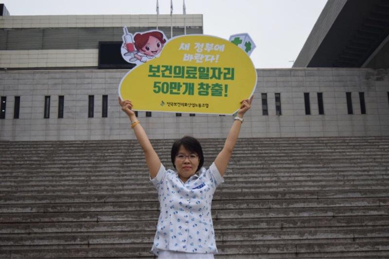 지난 5월 12일 세계 간호사의 날 기념, 일자리 창출 촉구 기자회견에서 한미정 보건의료노조 사무처장이 피켓을 들고 있다.
