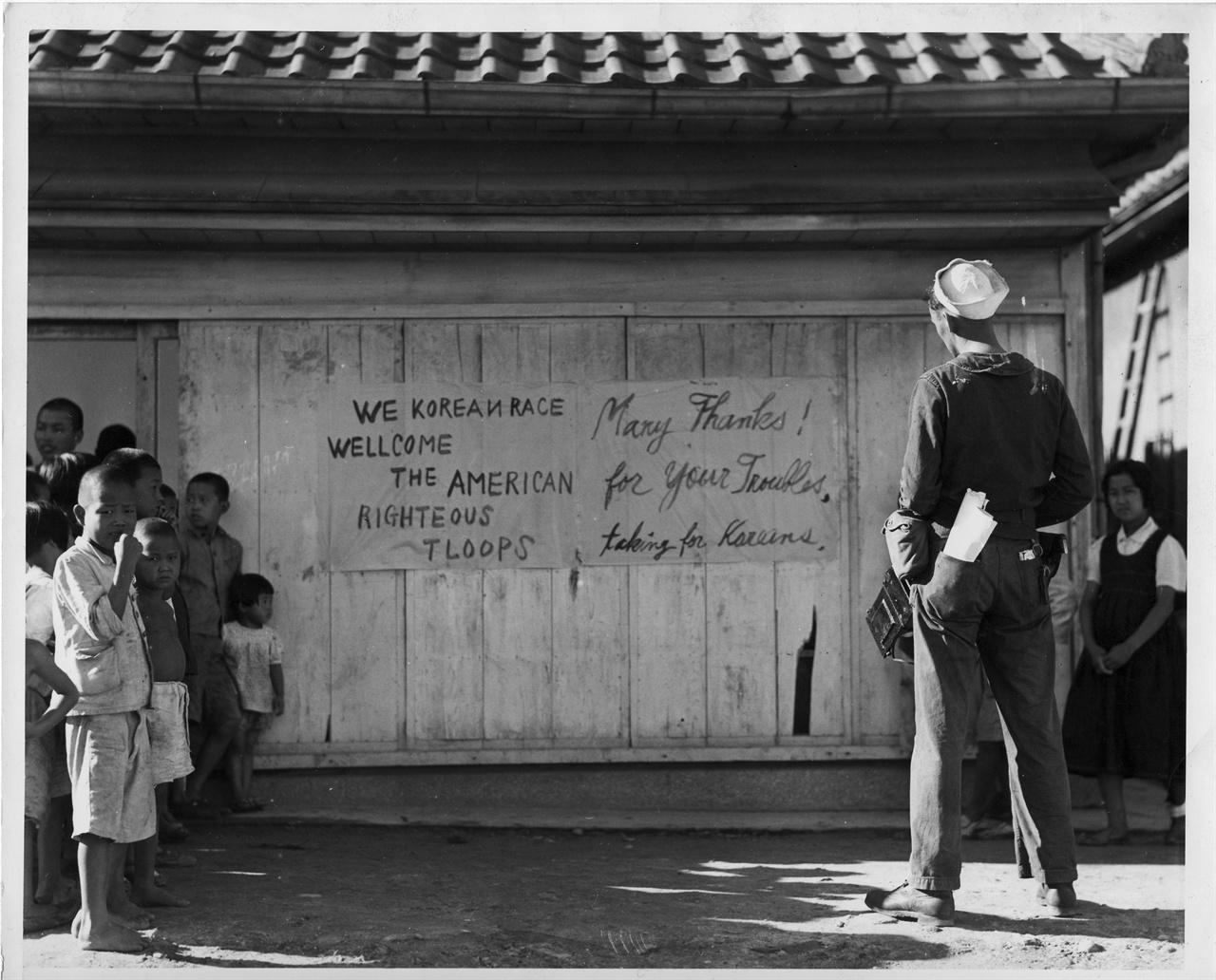 """1945. 9. 16. 한 미군이 """"한국인은 미군을 환영한다""""는 게시판을 바라보고 있다."""