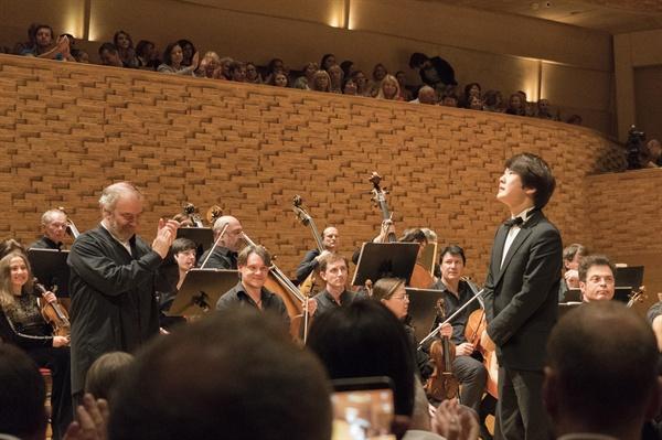 공연후 조성진이 관객에게 인사하고 있다. 지휘를 맡은 게르기예프가 흐뭇한 웃음을 지으며 함께 박수를 치고 있다.