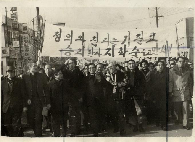 1975년7월20일, 지학순 주교(가운데 꽃다발 쓴 이)와 김지하 시인(지 주교 오른쪽)이 환영인파와 함께 원동성당을 향해 가두행진 중이다.