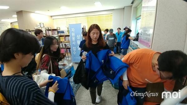 수해복구 작업을 위해 지원 물품을 받는 자원봉사자들