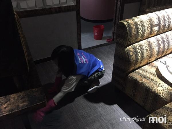 수해로 인해 젖은 노래방 바닥 타일을 닦고 있는 자원봉사자들