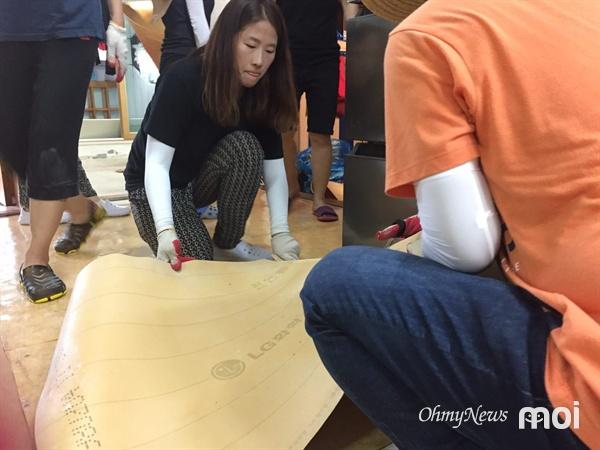 물기가 제거된 바닥에 장판을 깔고 있는 우리미래 김소희 공동대표