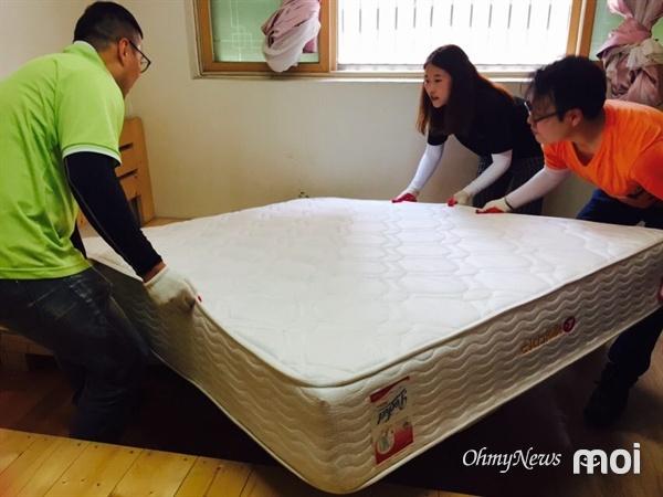 물기가 제거된 방에 침대를 들여놓는 자원봉사자들