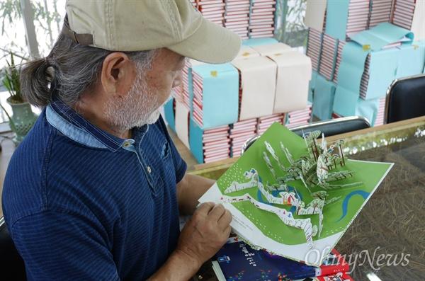 팝업북 <나무늘보가 사는 숲에서>를 들여다 보고 있는 보림출판사 권종택 대표.