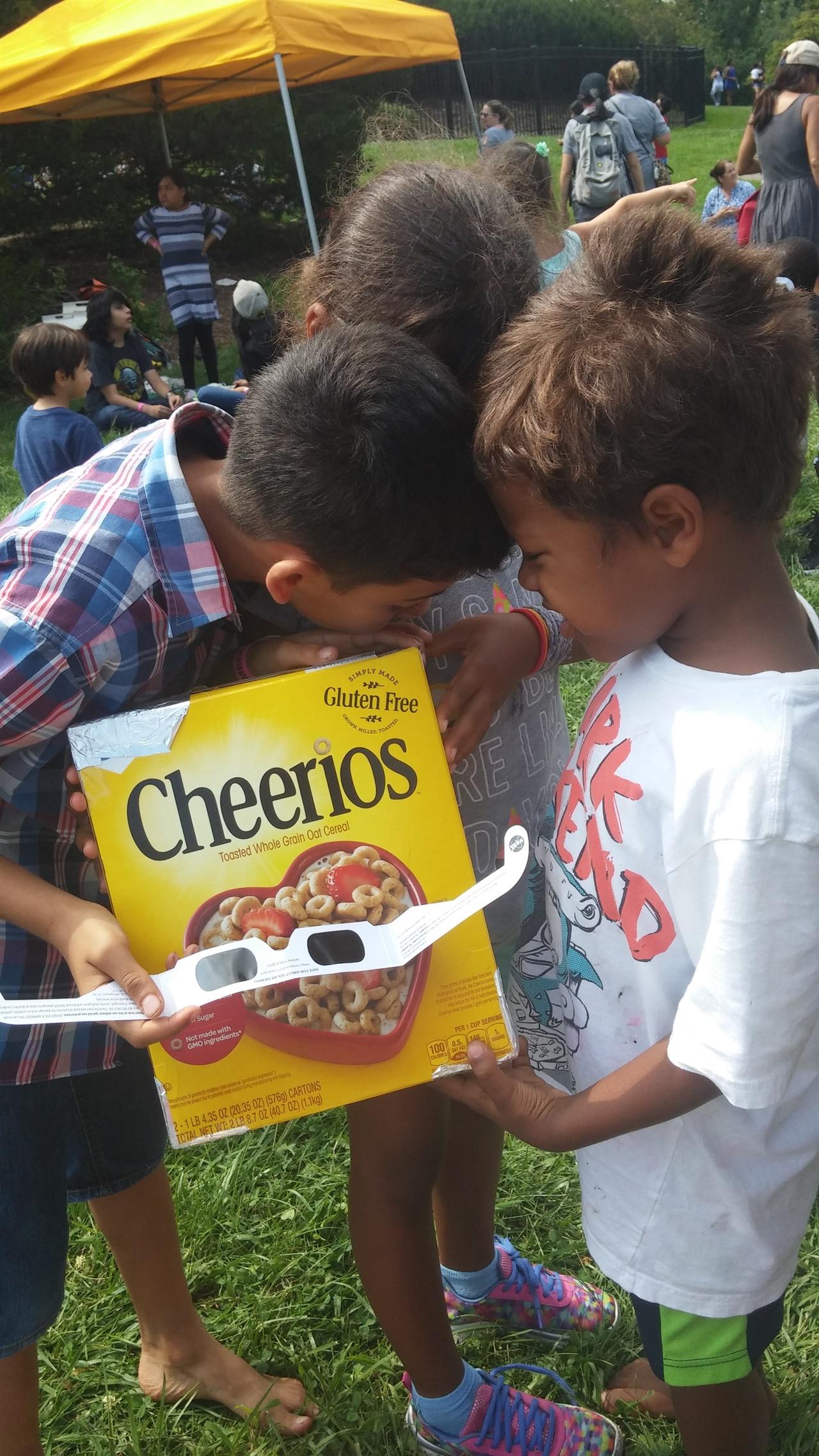어린이들이 씨리얼 상자로 직접 만든 망원경으로 개기일식을 보고 있다.