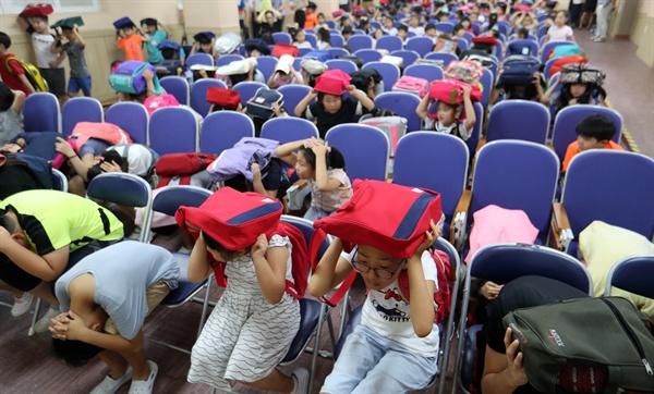 민방공 대피훈련을 한 23일, 대전 둔원초등학교 학생들이 공습 경보가 울리자 지하 강당으로 대피해 안내 방송에 따라 책가방을 머리 위로 올리고 낮은 자세로 대기하고 있다.