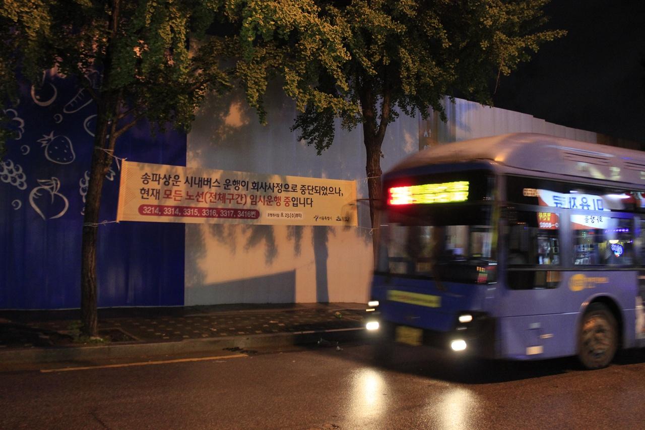 송파상운 운행중단 현수막 앞으로 대체버스가 지나고 있다.