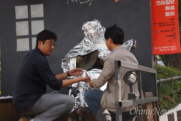 김광석길 만들기에 참여했던 작가들이 김광석 조형물을 은박지로 감싸는 퍼포먼스를 진행하고 있다.