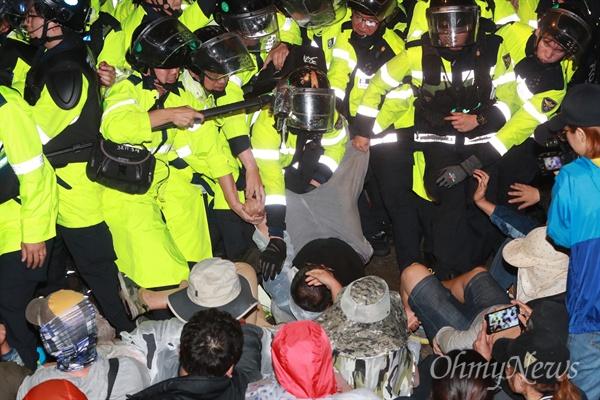 7일 사드배치를 앞둔 성주에서 경찰이 스크럼 짜고 있는 시민들을 한 명씩 뜯어내고 있다.