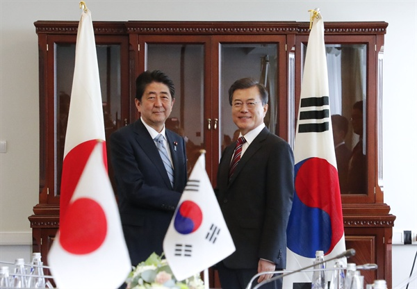 문재인 대통령이 7일 오전 동방경제포럼이 열리는 러시아 블라디보스토크 극동연방대학에서 아베 신조 일본 총리를 만나 악수하고 있다.