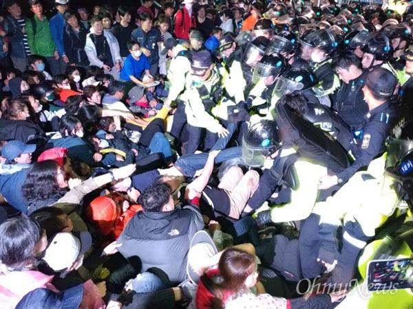 지난 7일 오전 경북 성주군 초전면 소성리 마을회관 앞에서 경찰이 사드 반입에 반대하는 주민들을 끌어내고 있다.