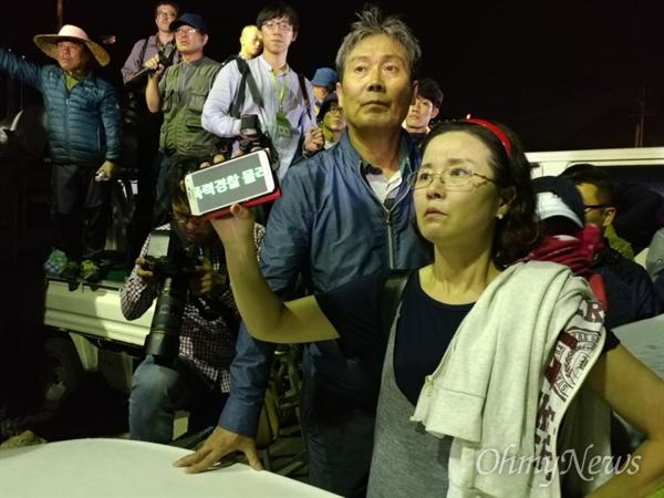 지난 7일 오전 경찰이 사드 반입을 저지하려는 주민들을 무차별적으로 끌어내자 한 여성이 흐마트폰에 '폭력경찰 물러가라'는 글을 써 들어보이고 있다.