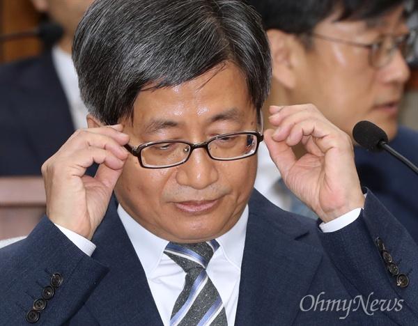 김명수 대법원장 후보자가 12일 국회 인사청문회에 출석해 안경을 고쳐쓰고 있다.