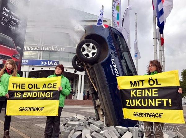 유럽 각지에서 온 그린피스 활동가들이 12일(현지시간) 독일 프랑크푸르트 모터쇼 행사장 앞에서 '자동차 내연기관 시대 막을 내리고 있다' 프래카드를 들고, 친환경 자동차 보급 등을 요구하며 퍼포먼스를 벌이고 있다.