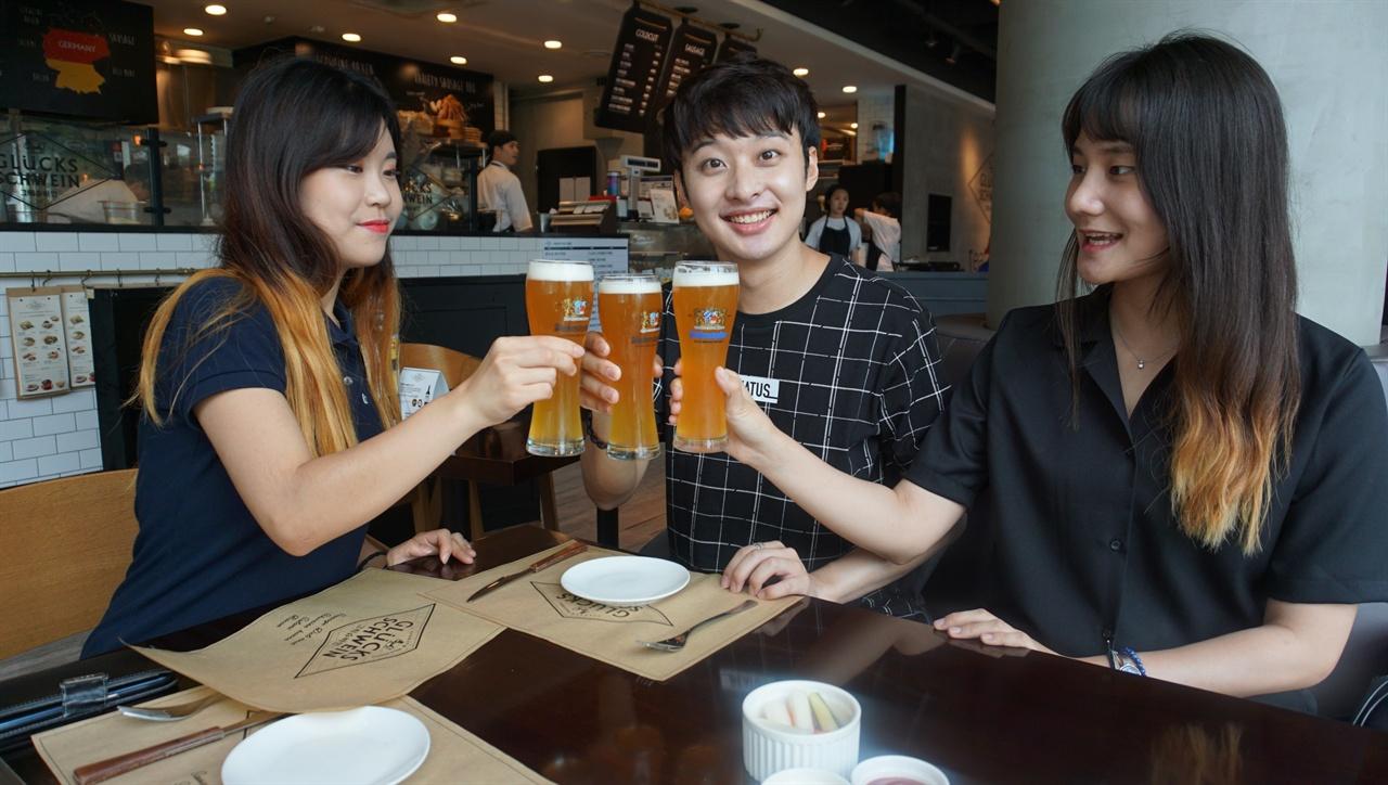 """""""독일 맥주 한 잔"""" 독일 글쓰기 교육을 주제로 좌담회를 하던 윤지영. 조영인. 윤세영 씨가 독일 맥주를 마시기 전에 건배를 하고 있다."""