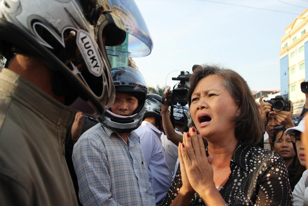 캄보디아 제1야당 부총재 무 소쿠아 의원이 오토바이헬멧을 쓴 진압경찰들을 향해 무고한 시민들을 폭행하지 말아달라고 간절히 부탁하고 있다. (2014년 1월 프놈펜 법원앞 )