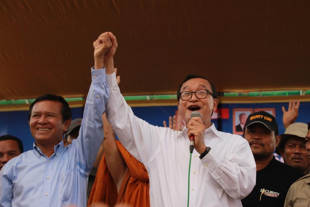 양손을 쥔 채 지지자들에게 인사를 하는 캄보디아 구국당 전현직 총재들의 모습 여당주도로 금년 2번에 걸쳐 개정된 선거법으로 인해 삼 랭시 총재(오른쪽)는 지난 2월 자리에서 물러났으며, 후임 켐 소카 총재는 국가반역죄로 징역 30년형 위기에 처해있다.