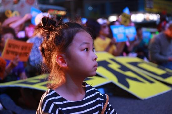 저녁 늦게까지 이어진 탈핵 집회에서 진지하게 연설을 듣고 있는 어린이