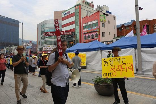 '동성애는 성적 타락'이라고 적힌 피켓을 든 사람 앞으로 십자가를 든 사람이 지나가고 있다.