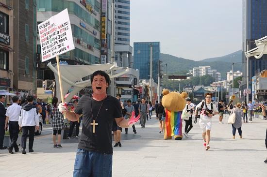 """""""하나님 앞에 동성애는 죄악이다""""라고 외치는 한 남성 뒤로 다양성을 상징하는 무지개 망토를 쓴 인형탈이 지나가고 있다."""