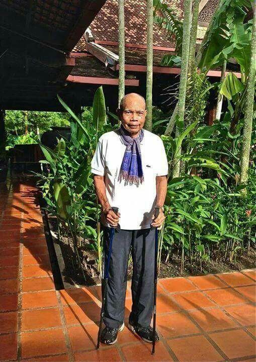 """2014년 건축사로서 은퇴를 선언한 후 수도 프놈펜에서 앙코르와트가 있는 씨엠립으로 이주한 그가 자택앞에서 지팡이를 쥔 채 사진촬영에 응한 완 몰리완의 모습. 그는 수년전 인터뷰에서 자신이 지은 건물들이 사라져가는 현실에 대해 """"너무나 슬프다""""고 말했다."""